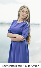 Young attractive beautiful blonde girl in a blue dress standing near water and looking aside