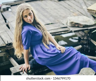 Young attractive beautiful blonde girl in blue dress sits on the boards near the wooden pier. She looks aside