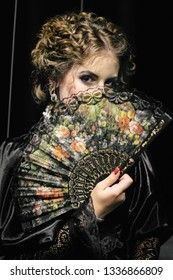 Young attractive beautiful girl with curly hair in black dress covers her face with a fan. She looks at the camera