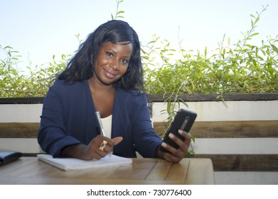 young attractive black African American woman sitting outdoors at coffee shop working busy and happy with internet mobile phone texting in entrepreneur and remote networking concept