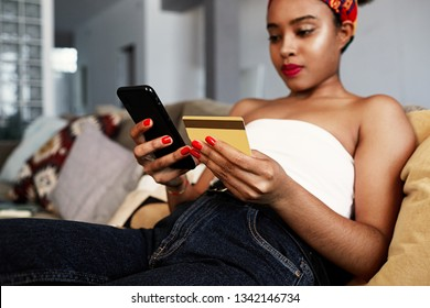 Young attractive black african female holding hands credit card and mobile phone hands. Technology, internet banking, e-commerce and online shopping