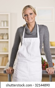 Young attractive blond with apron in the kitchen, leaning on the counter.
