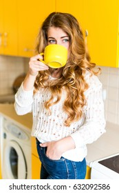 Young attractive blond girl in a yellow kitchen holding a cup of hot drink. Coffee or tea. The modern concept of blogging. Coffee break and relax