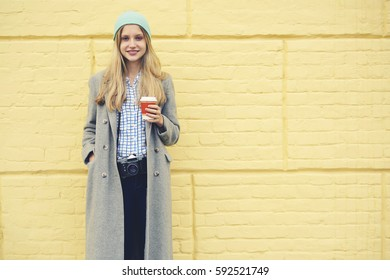 Young attractive blond hipster girl dressed in trendy streetwear outfit enjoying weekend trip  waiting for best friends to strolling together standing on copy space for your advertising with coffee