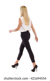 Young attractive blond woman in elegant white shirt, black pants and high heels walking. Rear view. Full length studio shot isolated on white.