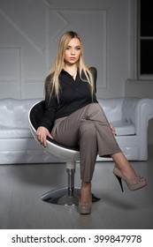 Young attractive blond woman wearing business clothes sitting on a chair