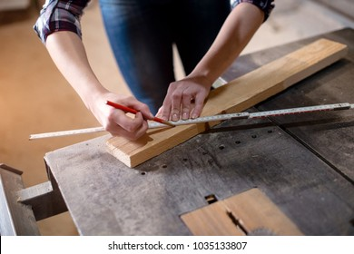Young attractive blond woman is working in carpenter workshop