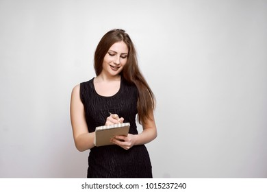 Young attractive blonde businesswoman holds black leather diary, isolated on white. Portrait of a beautiful blonde with a note and a pen in his hands