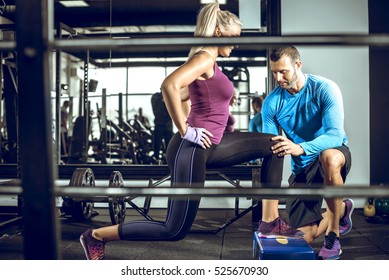 Young attractive blonde female doing lunge exercise in modern fitness center with assistance of her personal trainer.