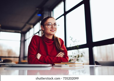 Young attractive blonde female in stylish eyeglasses dreaming whine sitting in loft interior place.Charming positive hipster girl dressed in red sweater looking away and thinking during recreating