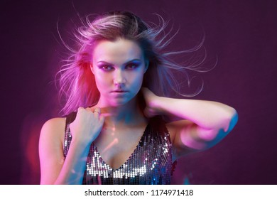 Young attractive blonde woman dancing in club, color light, motion effects. Black background, long exposure, Close-up portrait