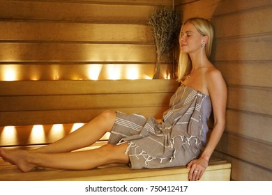Young attractive blonde woman relaxing in a sauna