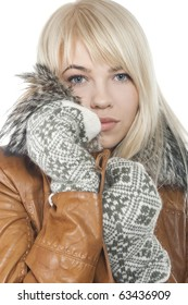 Young attractive blonde woman in warm mittens and coat with fur