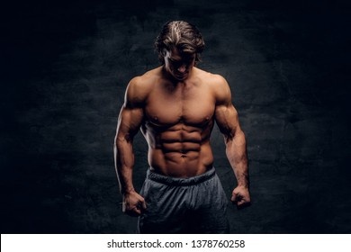 Young attractive bodybuilder with naked torso is posing for photographer on grey background.