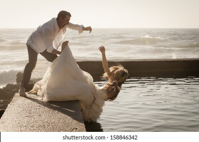 Young attractive bridal wedding couple falling into pool of water