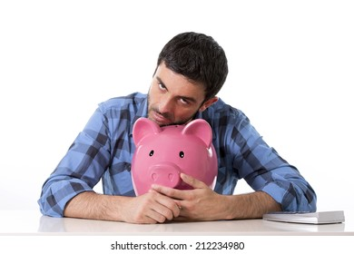 young attractive broke man worried in stress feeling sad hugging empty pink piggy bank in bad financial situation concept wearing casual shirt isolated on white background