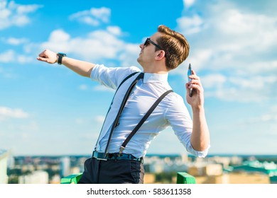 young attractive brunette caucasian businessman in white shirt, black tie, black braces, costly watch and black sunglasses stand on the green ladder on the roof, throw phone out