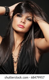 Young attractive brunette with long hair posing on black background.