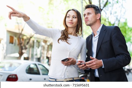 Young attractive brunette pointing to serious young man at something