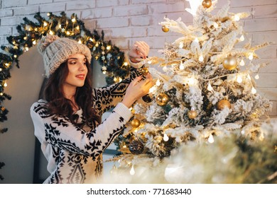 Young attractive brunette woman decorating Christmas tree in cozy home interior