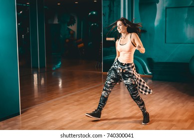 Young attractive brunette woman doing zumba dance workout alone in gym. Toned image.
