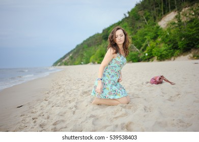 Young attractive brunette woman on a beach wearing dress