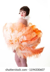 Young attractive burlesque dancer in sequin panties holding apricot feather fans