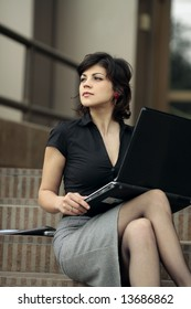 young attractive business lady outdoors with a laptop in her lap is looking far away