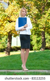 Young attractive business woman with documents standing outdoors