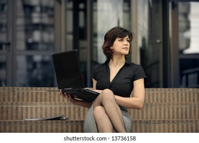 young attractive business woman with the laptop outdoors