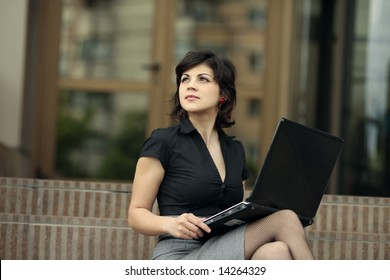 young attractive business woman with the laptop outdoors looking up