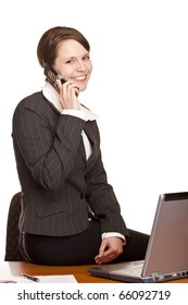 Young attractive business woman talks in office with mobile phone. Isolated on white background.