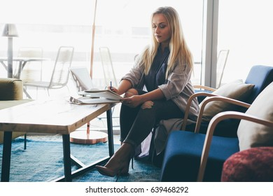 Young attractive business woman working in a cafe during the lunch break. Entrepreneur is searching for information in the Internet by using a laptop and makes notes in a notebook.