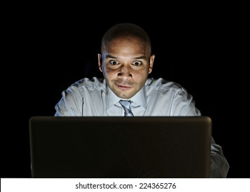 young attractive businessman alone at night sitting at computer laptop watching porn or online gambling isolated on black background on internet chat addiction concept