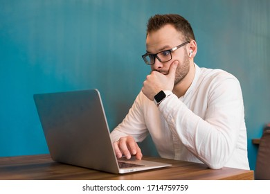 Young attractive businessman in glasses, with a beard, headphones and a wristwatch, looks in surprise at the laptop on a blue background