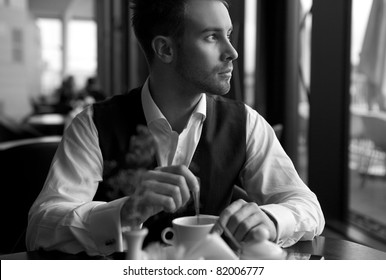 young attractive businessman has coffee a pause. Black-white photo.