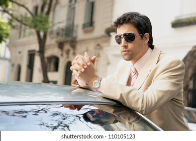 Young attractive businessman leaning on the top of a car in a classic street, wearing sunglasses.