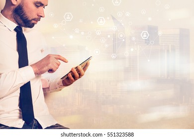 Young attractive businessman on the background of buildings and technology patterns.