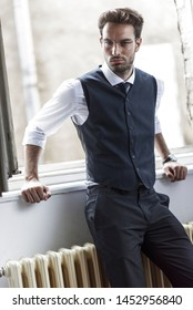 Young and attractive businessman posing next to a window, looking sexy and confident