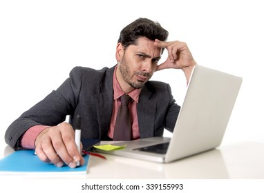 young attractive businessman sitting at office desk working on computer laptop looking bored and worried in work stress and business problems concept