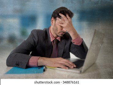 young attractive businessman sitting at office desk working on computer laptop covering his face desperate and worried in work stress and business problems concept grunge edit