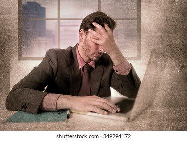 young attractive businessman sitting at office desk working on computer laptop depressed and desperate suffering headache looking frustrated and sad in grunge dirty edition background