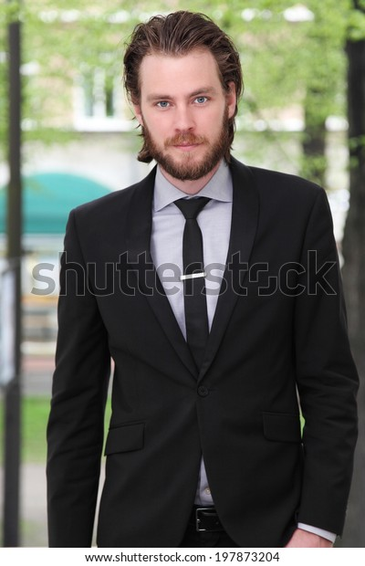 Young attractive businessman standing in front of a green city background.