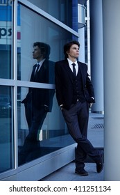 Young attractive businessman standing at office building