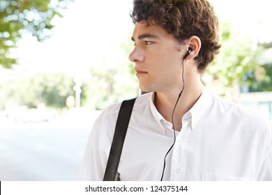 Young attractive businessman standing in a wide city avenue with his headphones in his ears, outdoors.