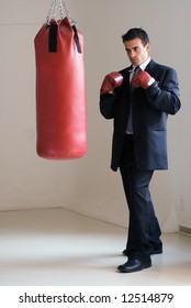 Young attractive businessman in a suit wearing boxing gloves standing ready in front of a heavy punching bag