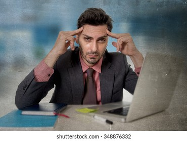 young attractive businessman working on computer laptop at office desperate and worried suffering headache in work stress and business problems concept grunge edit