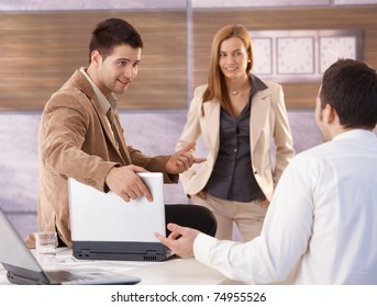 Young attractive businesspeople talking in office, smiling.?