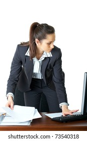 young attractive businesswoman checks her computer and papers, isolated on white