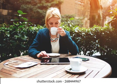 Young attractive businesswoman at coffee time working on digital tablet while sitting on the terrace of coffee shop, caucasian blond well dressed woman using touch pad while sitting in coffee shop